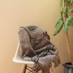  Handmade light grey blanket draped over a white chair next to a big plant