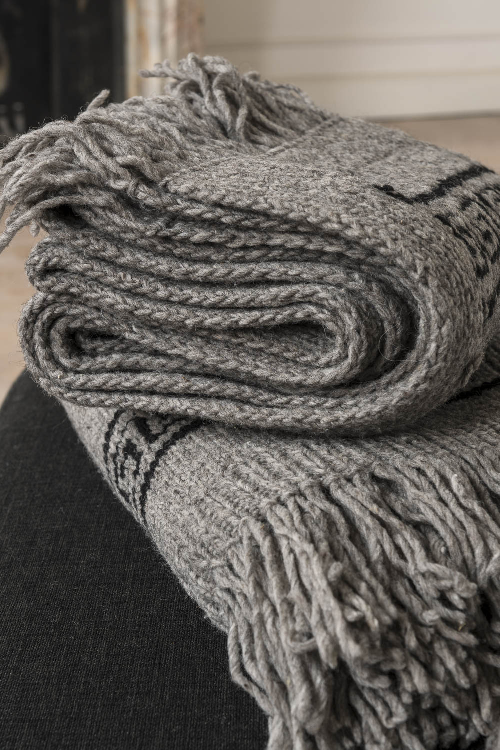 Close-up of two Tutamanta handmade wool blankets in light grey folded on top of each other