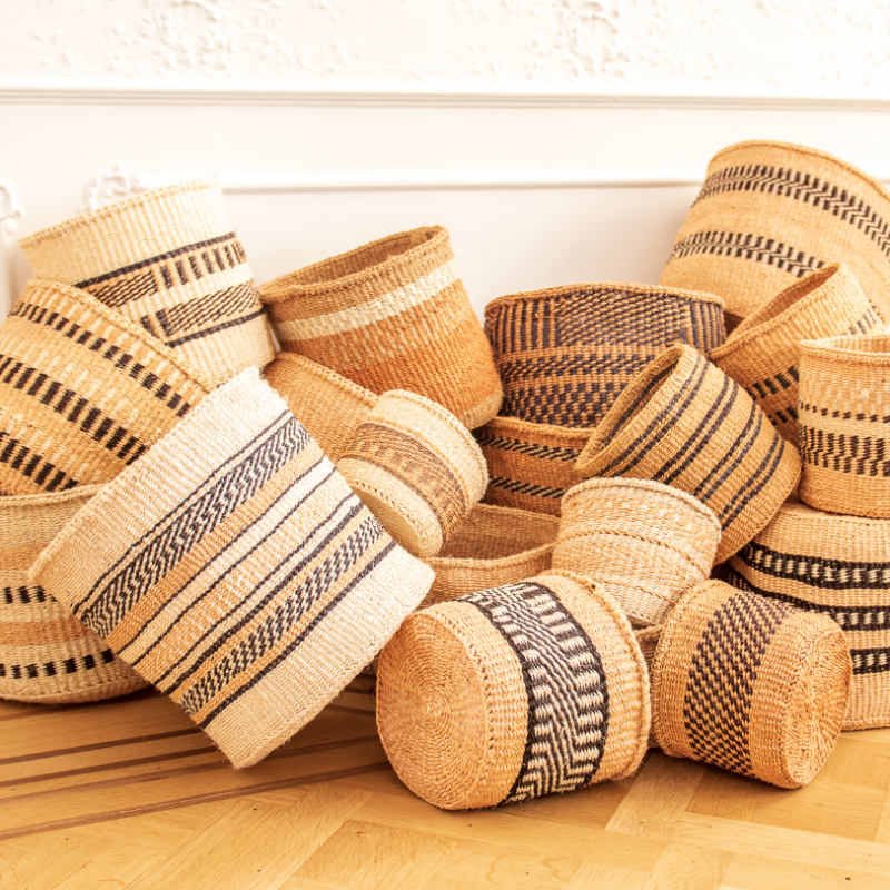A pile of handmade Sisal baskets in natural tones on a wooden floor