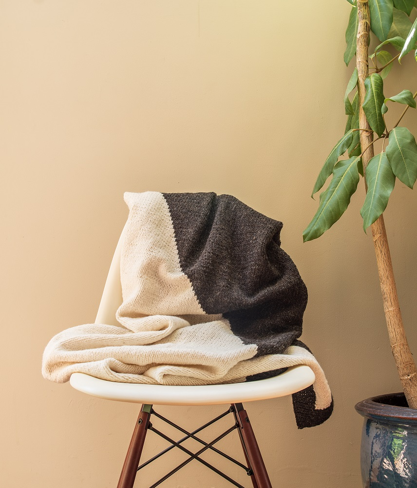 Handmade black & white blanket draped over a white chair next to a big plant