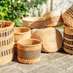 Several handmade baskets in natural tones put together on a terrace outside